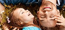 꽃 밭에서 어린 아이와 아빠가 누워서 행복하게 웃는 사진