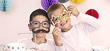 식탁 위에 별 모양이 있는 컵과 접시 등이 있으며 어린이 2명이 장난기 가득한 얼굴로 콧수염 가면과 별 가면을 쓰고 있는 사진