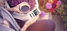 여성이 왼손에 커피가 든 잔을 들고 오른손에는 제주신라호텔 모바일 메인 화면이 떠 있는 휴대전화를 들고 있으며 주변에는 다양하고 예쁜 꽃들이 있는 사진